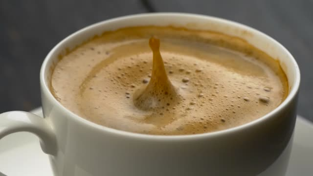 splashes of coffee in white espresso coffee cup. drops of coffee falls into the foam. close-up shot - coffee стоковые видео и кадры b-roll
