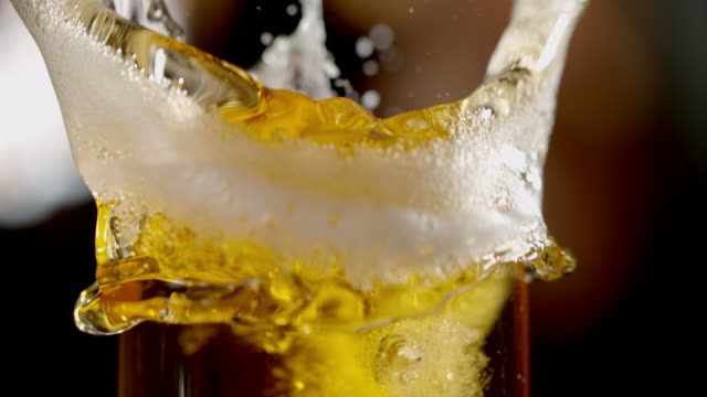 SLO MO Splashing beer in a glass Super slow motion close-up shot of beer splashing over a glass. lager stock videos & royalty-free footage