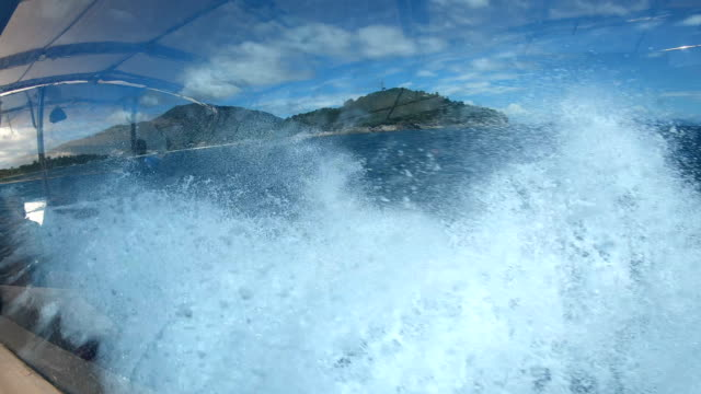 Splashing sea waves water hitting boat and Adang Island with blue sky seen from side view of speedboat moving on ocean