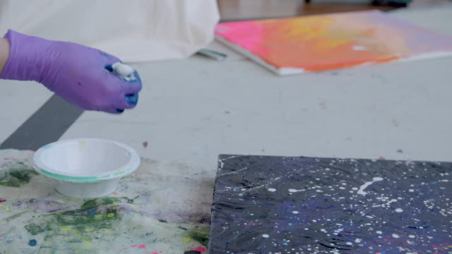 splattering white paint onto a canvas - pittore video stock e b–roll