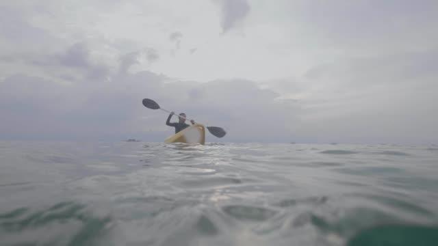 sualtı manzaralı sakin denizde kayık kürek çeken bir kadının bölünmüş fotoğrafı. - bölmek stok videoları ve detay görüntü çekimi