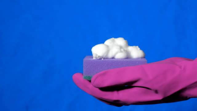 vídeos de stock e filmes b-roll de sponge in male hand in magenta rubber glove. white foam splashes out of the spray can. - esponja