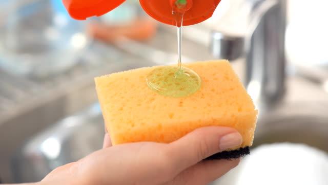 Sponge with dish washing liquid. Sponge with dish washing liquid. dishwashing liquid stock videos & royalty-free footage