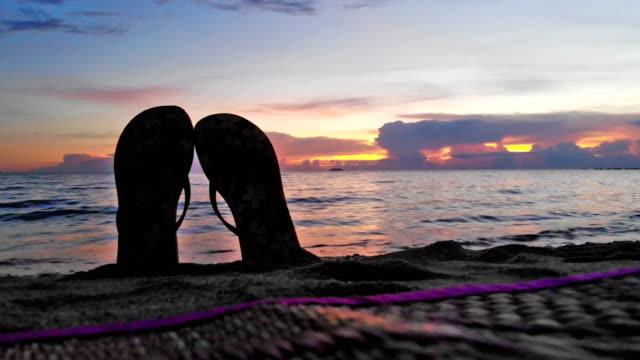 vídeos y material grabado en eventos de stock de esponjas se entierran en la playa con sol, puesta del sol y de onda - moda playera