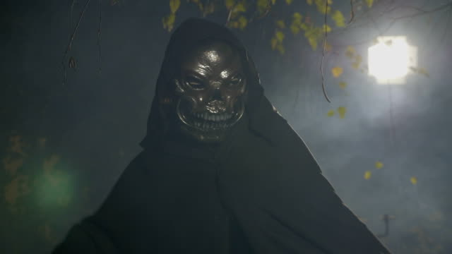Spooky dark zombie wearing a mask playing with his black cape attacking the camera in the halloween moonlight video