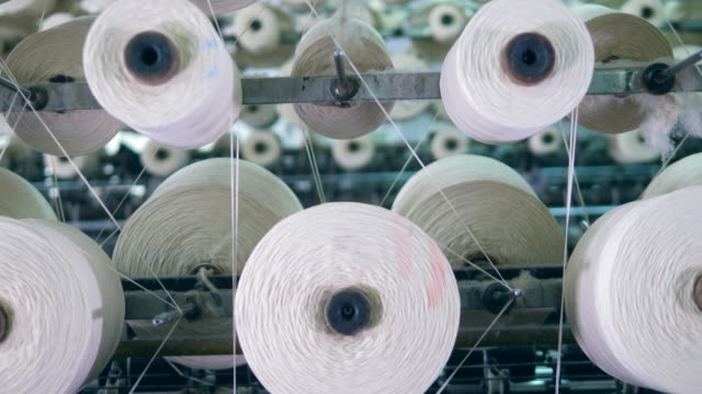spools are slowly spinning with white threads on them - cilindro video stock e b–roll