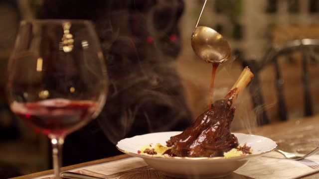 vídeos de stock e filmes b-roll de spoon pouring sauce on meat. cooked lamb knuckle . dark red sauce poured on meat of lamb in plate with salad . chef's table with glass of wine and cooking show inspired footage .  slow motion . - meat plate