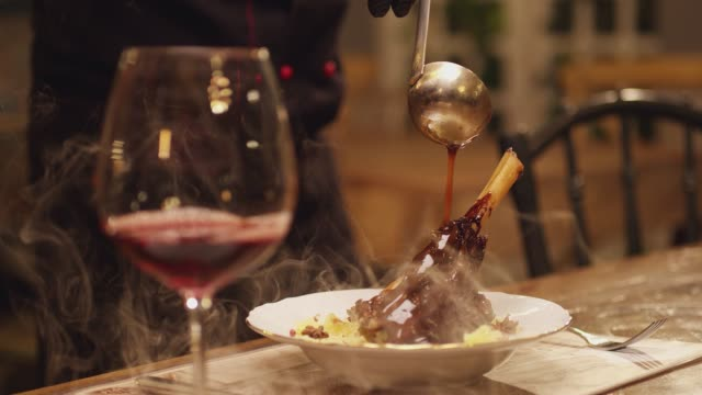 vídeos de stock e filmes b-roll de spoon pouring sauce on meat. cooked lamb knuckle . dark red sauce poured on meat of lamb in plate with salad . chef's table with glass of wine and cooking show inspired footage .  slow motion . - sauce