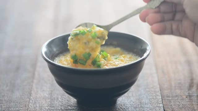 Spoon stirring and scooping rice congee