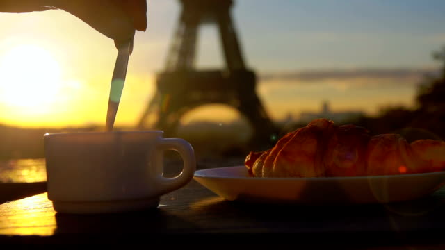 spoon stirs sugar in a coffee next to eiffel tower - cucina francese video stock e b–roll