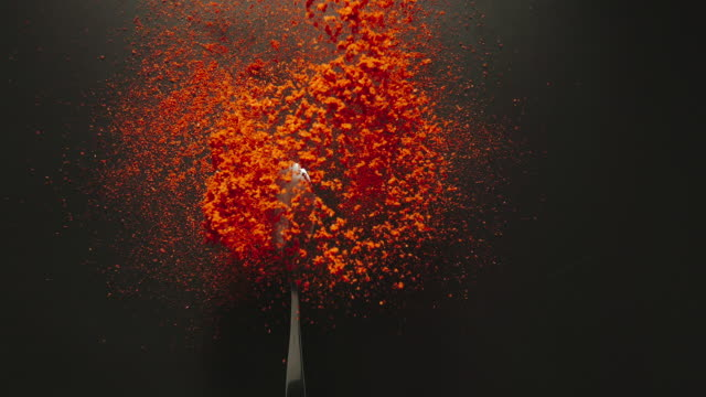 SLOW MOTION: Spoon with red pepper powder falling onto a black table