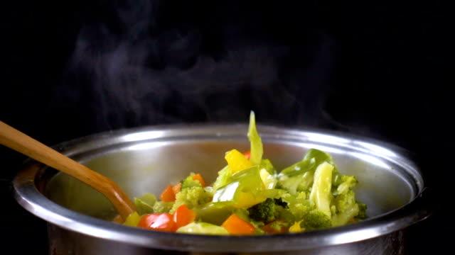 stockvideo's en b-roll-footage met lepel met groenten op pan met soep en stoom - groentesoep