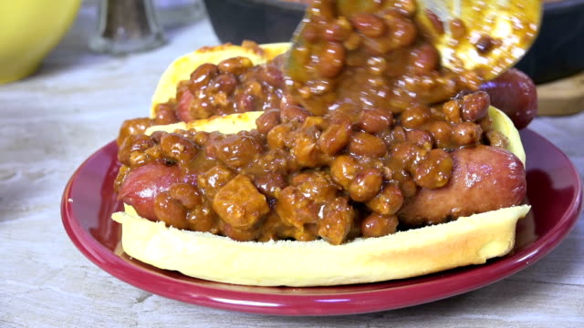 spooning chili con carne onto a hot dog - chilli con carne video stock e b–roll
