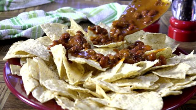 Spooning chili onto tortilla chips video