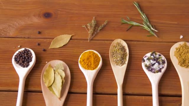 vidéos et rushes de cuillères avec différentes épices sur la table en bois - plante aromatique