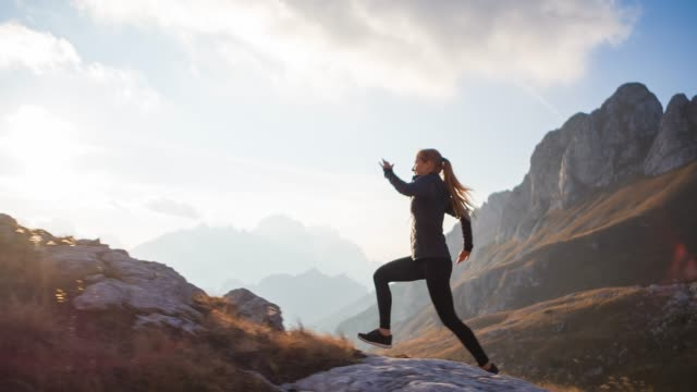 sport active woman running uphill over rocky trails and grassy slopes in mountain terrain - уход за фигурой стоковые видео и кадры b-roll
