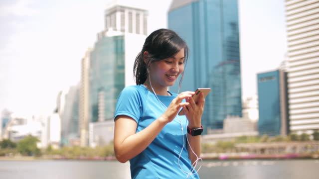 akıllı telefon kullanarak spor asyalı kadın - kulak i̇çi kulaklık stok videoları ve detay görüntü çekimi