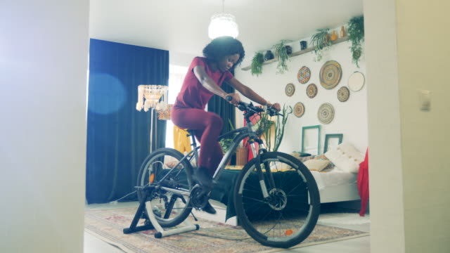 Sport at home, fitness at home concept. Cycling practice of an african lady during lockdown Cycling practice of an african lady during lockdown. 4K exercise bike stock videos & royalty-free footage