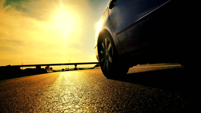 Sport car driving down narrow road toward sun rays at sunset, low angle back view