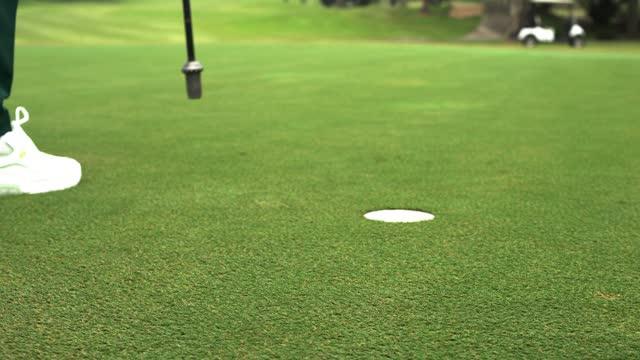 vidéos et rushes de homme de sport frappant la boule de golf au trou pour le score de par. - golf