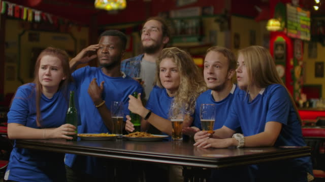 Sport, people, leisure, friendship and entertainment concept - happy football fans or male friends drinking beer and celebrating victory at bar or pub. – film