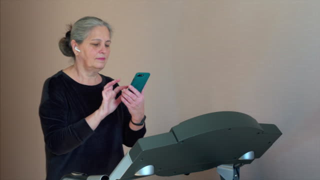 sport senior woman is training on treadmill in home and looking in mobile phone - runner rehab gym video stock e b–roll