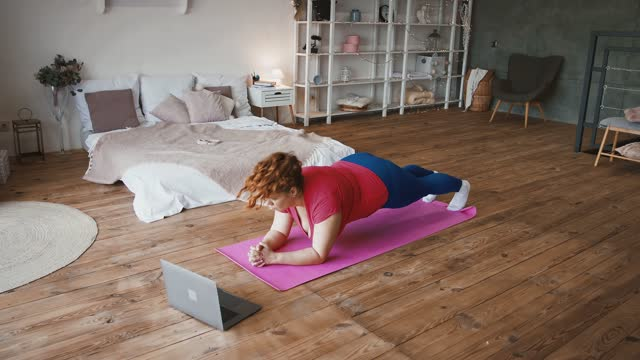 Sport tutorial. Young overweight lady doing plank exercise, watching online fitness lessons on laptop at home Sport training tutorial. Young overweight lady doing plank exercise, watching online fitness lessons on laptop at home bodyweight training stock videos & royalty-free footage