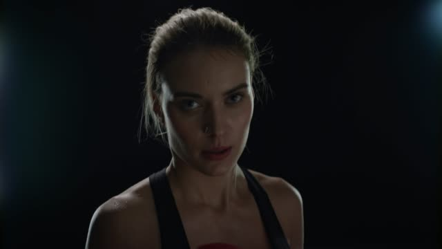 Sport woman doing punches in red boxing gloves at cardio training. Woman boxer Sport woman doing punches in red boxing gloves at cardio training in black studio. Portrait of woman boxer boxing front camera. Mixed martial arts. Fit girl kickboxing training martial arts stock videos & royalty-free footage