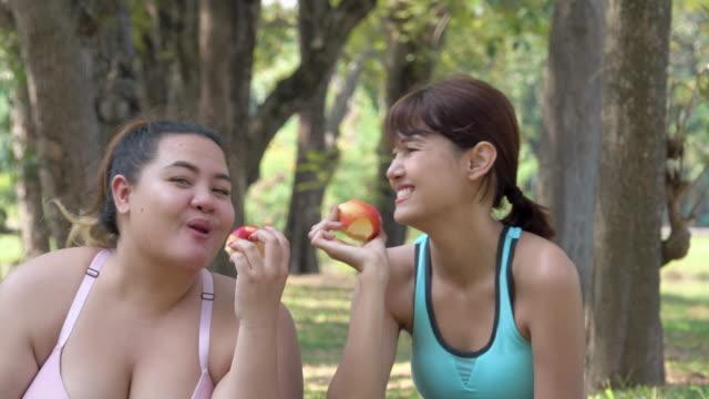 sport kvinna äter apple på park - gym skratt bildbanksvideor och videomaterial från bakom kulisserna