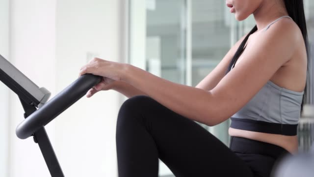sport woman legs exercising pedals of exercise bike in a gym - class стоковые видео и кадры b-roll
