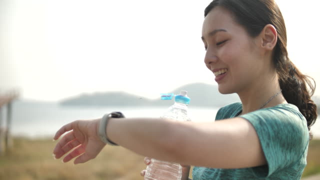 Sport woman looking on Smart watch and Drinking Water