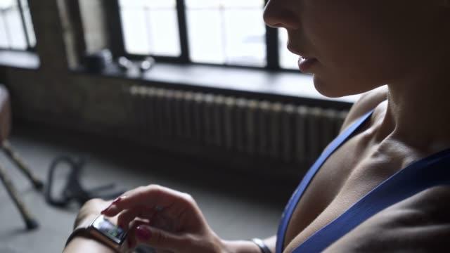 la donna dello sport guarda l'orologio intelligente in palestra - computer indossabile video stock e b–roll