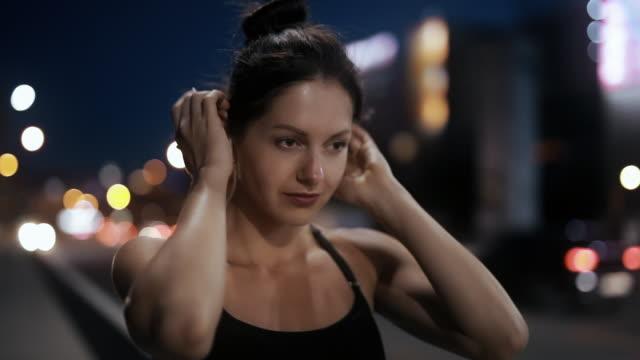 sport woman puts on wireless earphones and runs on a bridge - auricolari wireless video stock e b–roll