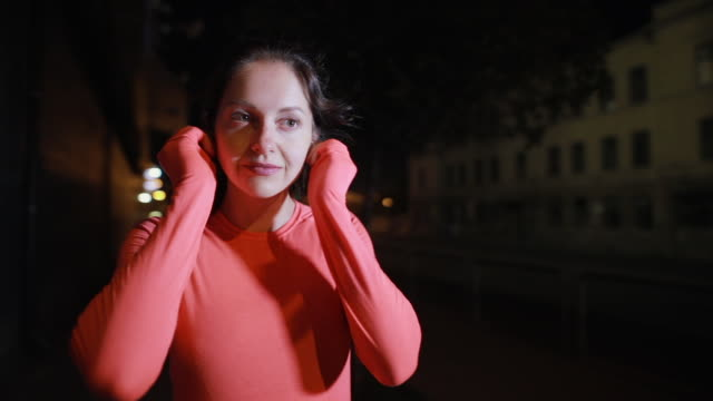 sport woman running along night city street puts on earphones - cuffie wireless video stock e b–roll