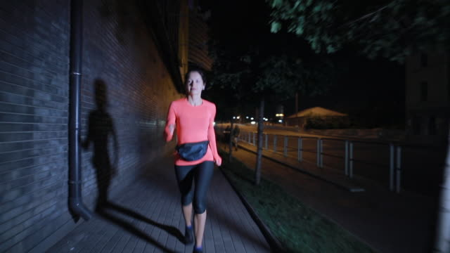 sport woman running along night city street with earphones - cuffie wireless video stock e b–roll