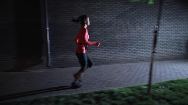 donna sportiva che corre lungo la strada notturna della città con gli auricolari - auricolari wireless video stock e b–roll