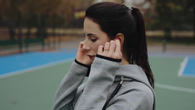 la donna sportiva indossa auricolari wireless all'inizio del suo allenamento - auricolari wireless video stock e b–roll