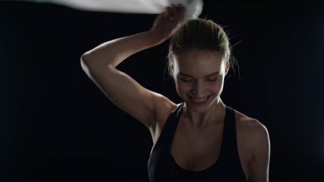 sport kvinna med handduk på axlarna poserar på svart bakgrund. tränings modell - black woman towel workout bildbanksvideor och videomaterial från bakom kulisserna