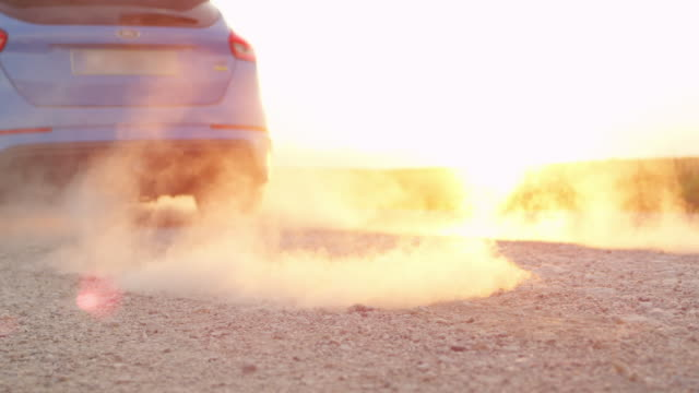 CLOSE UP Sportive auto scorching the tires with burnout on gravel road at sunset video