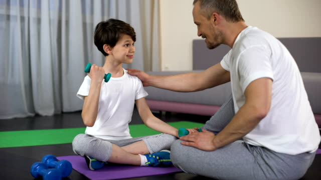 Sportive dad teaching his son to make dumbbells exercise at home, muscles power video