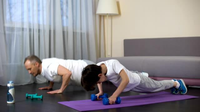 Sportive father teaching his son doing push-ups, military training, endurance video