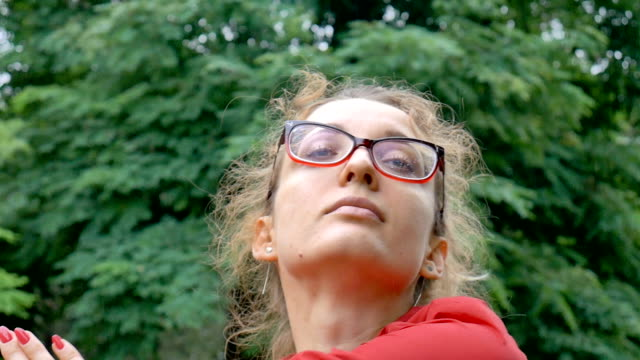 Sportive fitness girl in eyeglasses is warming out ready to exercise outside in the park during spring or summer morning under the rain. Healthy lifestyle concept