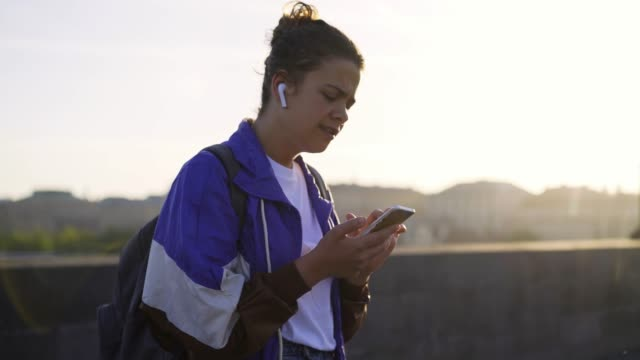 Sportive girl in backlit listening music on street in backlit
