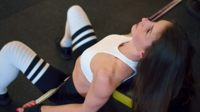 Sportive girl working out hip thrust with barbell video