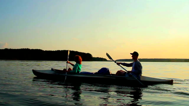 Sportive man and woman paddling boat synchronously, active rest video