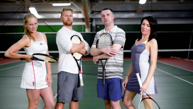 Sportive men and women posing with rackets on tennis court video