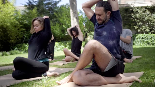 Sportive people performing yoga pose in park Sportive people performing yoga pose in park. Flexible men and women sitting on yoga mats and practicing yoga. Yoga concept mental wellbeing stock videos & royalty-free footage