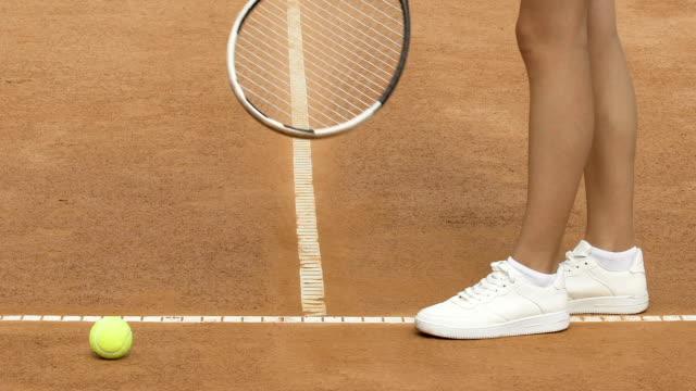 Sportive slim girl preparing before tennis game, outdoor trainings, close up video