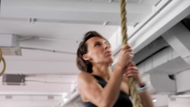 sportive woman is climbing on rope in gym. strength workout, sport concept. - inerpicarsi video stock e b–roll