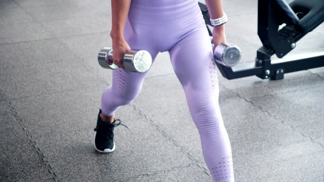 Sportive woman is doing lunges for legs with dumbbells in her hands in gym, legs closeup.
